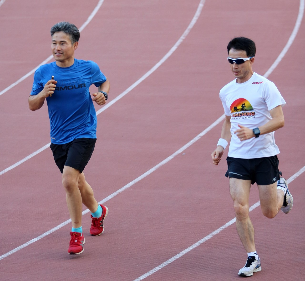 2 boys running on a race track