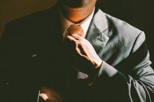 business man adjusting tie - CollegeMarker