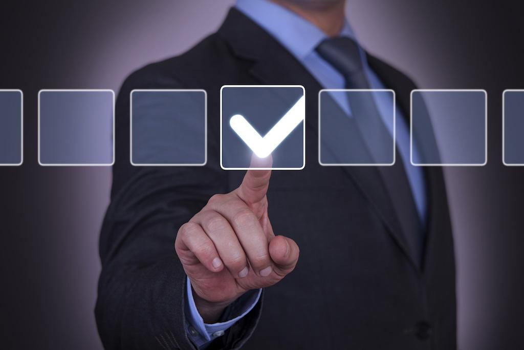 businessman clicking on checklist - CollegeMarker